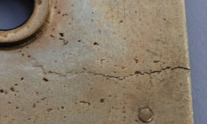 A nasty crack in the cast brass plates that were hammered and smoothed by hand.
